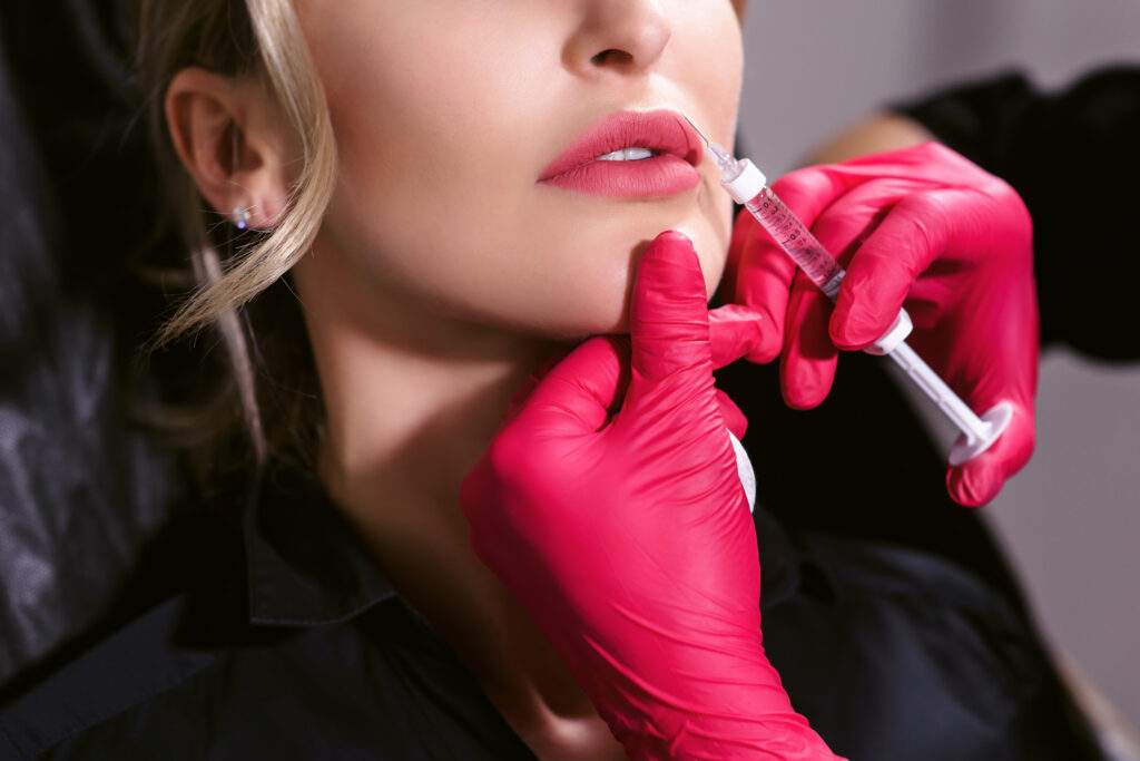 Lips injection in beauty clinic. Female beautician doctor with syringe in hands making cosmetological procedure with young woman patient in office.