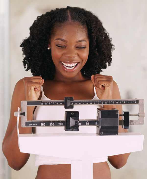 woman standing on scale excited about weight loss